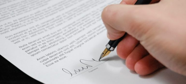 A person signing a binding long distance moving estimate.