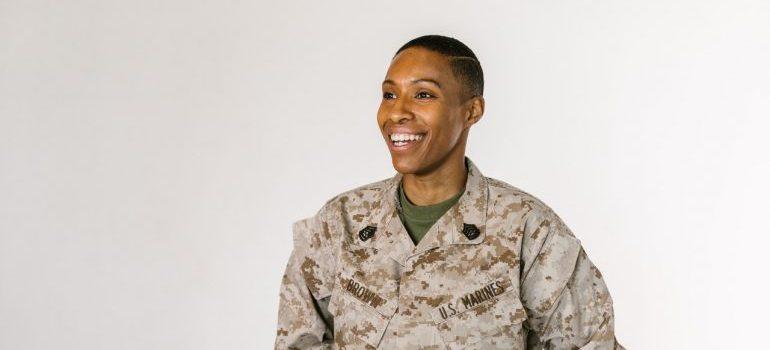 A smiling soldier in desert camo uniform