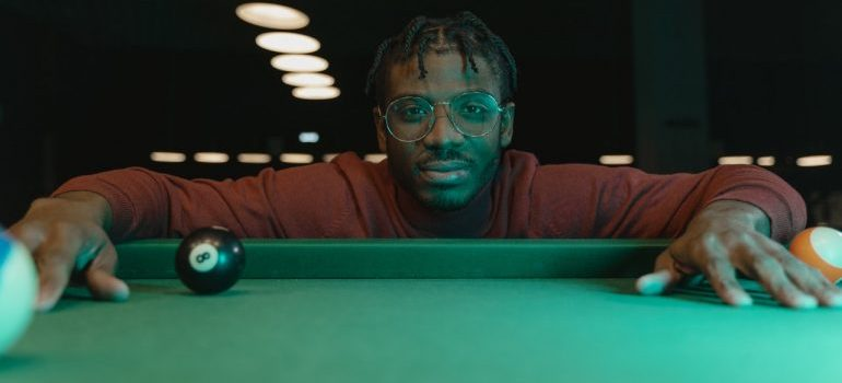 A man resting his hands on the pool table