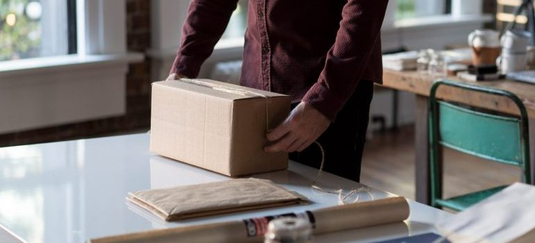 person packing a cardboard box