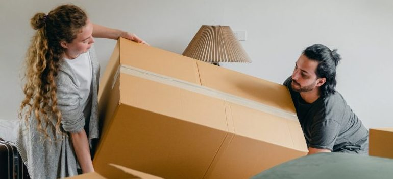 a couple lifting a large cardboard box