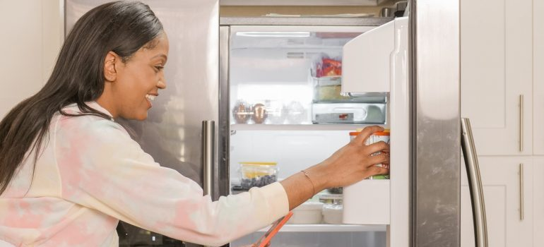 A woman next to a fridge, figuring out how to protect kitchen appliances when moving.
