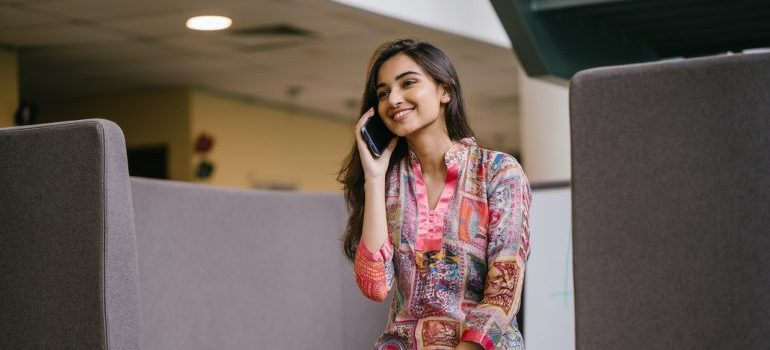 A smiling woman talking on the phone after moving off to college.