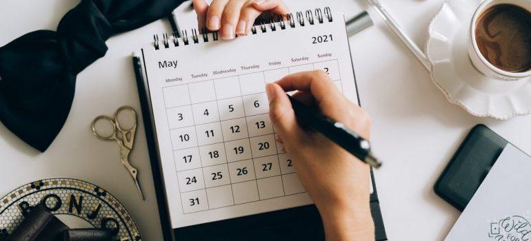 Person writing on a calendar