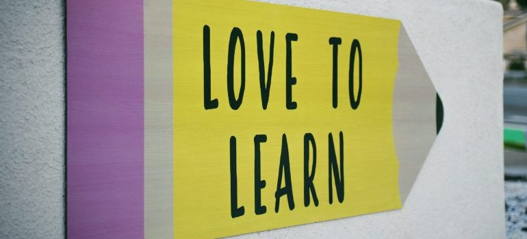 """yellow-purple colored board, stating """"LOVE TO LEARN"""""""
