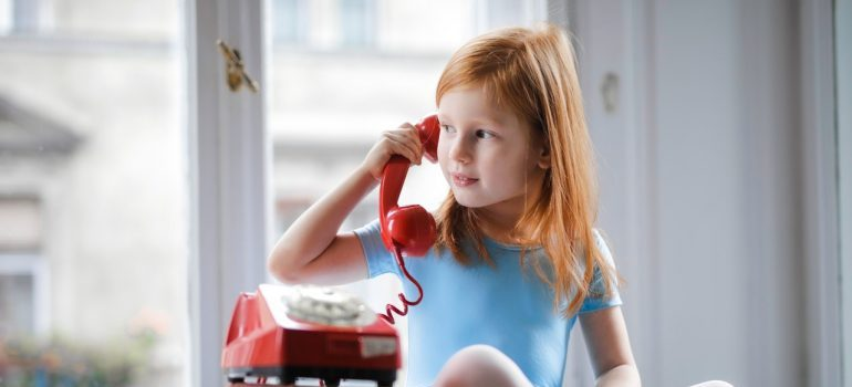 A little girl in a blue dress playing with a red phone