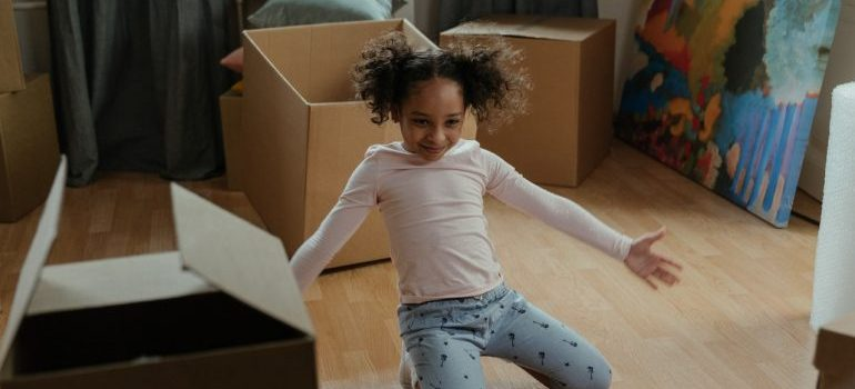 A smiling kid among moving boxes.