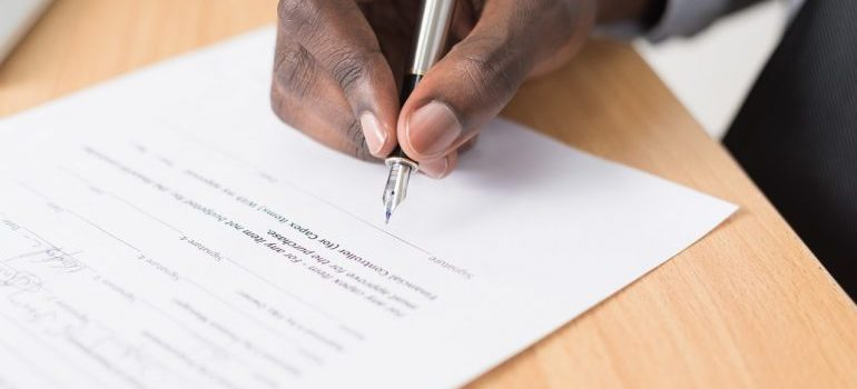Person checking a document before signing it to avoid most common shipping delays