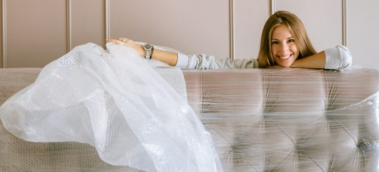 A smiling woman holding sheet of bubble wrap.
