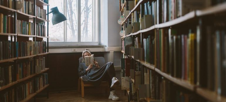 A woman reading about the ways of relocating your home library.