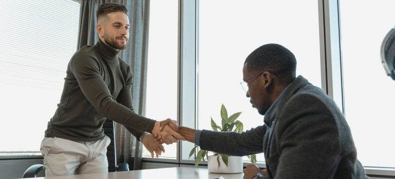 A businessman shaking employees hand.