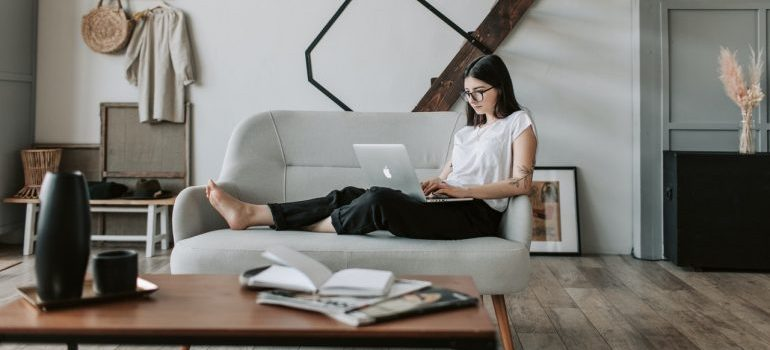 Woman using laptop to research ways of moving without damaging her home.