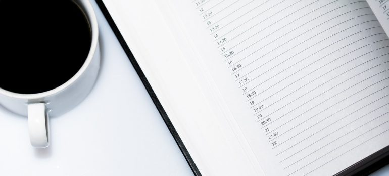 A cup of coffee next to a personal planner to help you plan a post-moving cleanup.