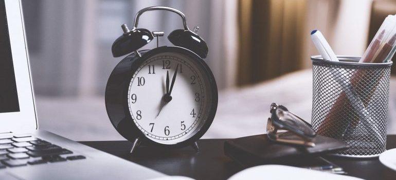 A black alarm clock on the table.