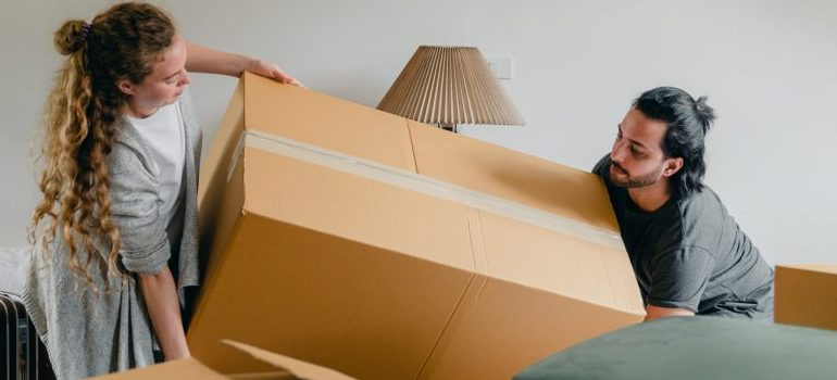 a couple moving a large cardboard box